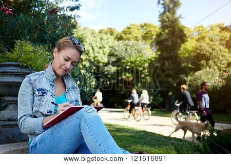 Young charming female is writing something in her diary while is relaxing in the fresh air during recreation time woman student is preparing to college tuition while is sitting with notepad outside