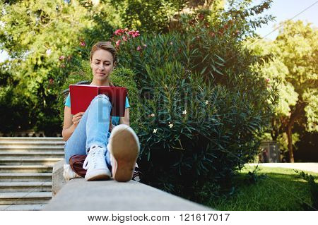 Gorgeous young woman is reading interesting book during her recreation time in summer weekend attractive female student is preparing for college tuition while is sitting alone in beautiful green park