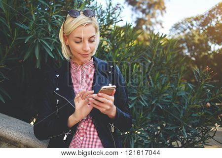 Young blonde female is chatting on her mobile phone, while is standing in beautiful park in spring day