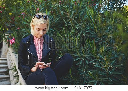 Stylish female student chatting on cell telephone in network while sitting in the fresh at university campus hipster girl watching gallery photos on her smart phone while sitting outdoors in the park