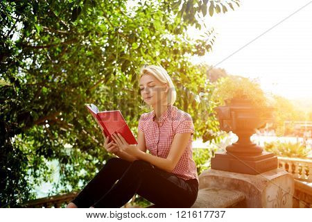 Gorgeous Caucasian female student is reading interesting book in spring day after her lectures in university beautiful blonde woman is learning outdoors during recreation time in summer weekend