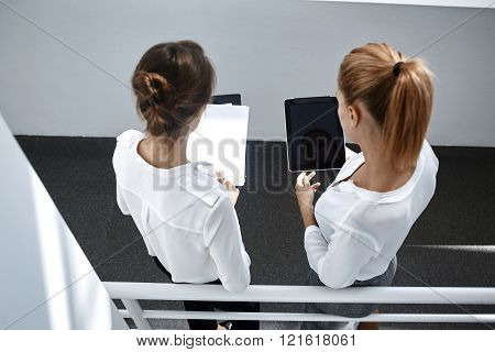 Top view of women skilled architects are holding touch pad and paper documents with mock up copy space for advertising content.Two female are checking the information from contracts and digital tablet
