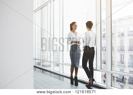 Two female successful architects are talking about joint project while are standing in hallway company near window. Young women economists dressed in formal wear having conversation during work break