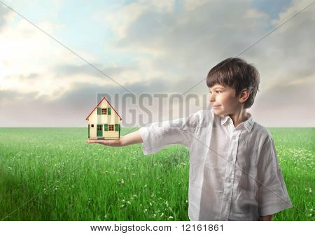 Smiling child holding the model of a house on a green meadow