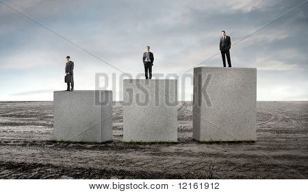 Three business people standing on cubes of different height