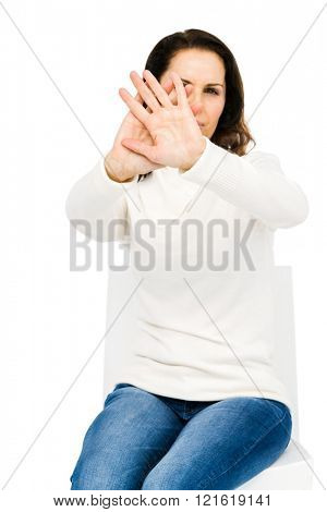 Unhappy woman hiding her face with hands against white background