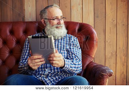bearded senior man sitting with tablet pc with good mood