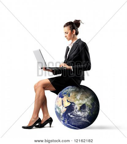 Businesswoman sitting on the earth and using a laptop