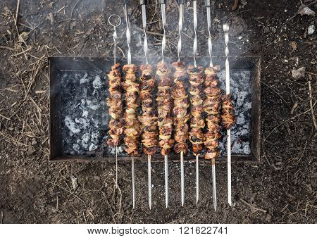 Appetizing fresh meat shish kebab prepared on a grill wood coal. Top view of cooking shashlik