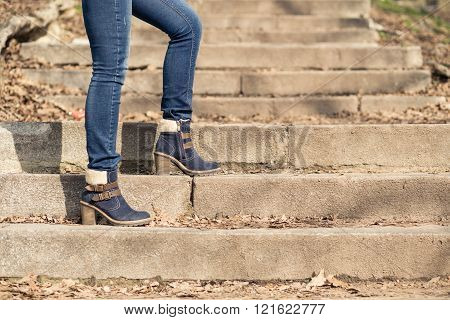 Female Legs In Winter Boots And Jeans On Stairs