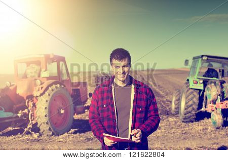 Young handsome farmer standing on farmland. Tractors working in background
