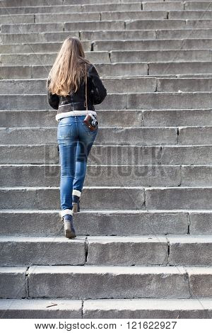 Young Woman With Old Camera Steps Upstairs