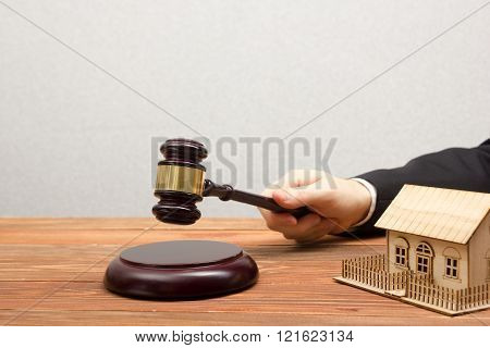 Auction, Real Estate concept. Hand with judge gavel and house model
