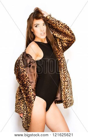 brunette posing in leotard and leopard skin coat