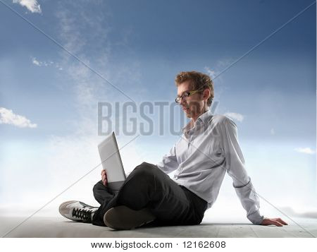 Young man with laptop on his knees