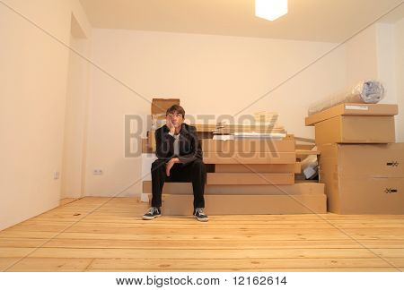 Young man sitting on a pile of furniture packing in an empty flat