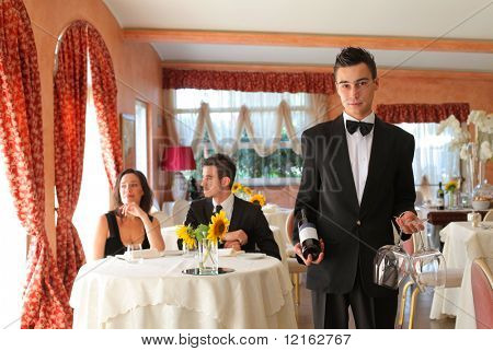 Young waiter in a restaurant with couple on the background