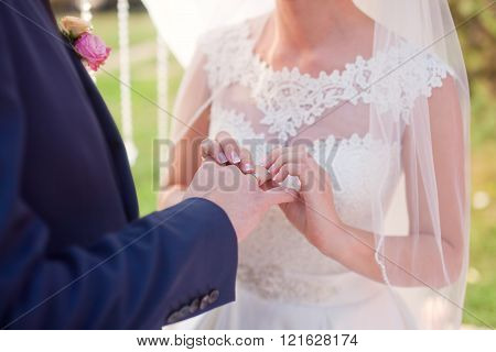 The bride wears a wedding ring on finger of the groom