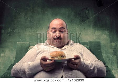 Hombre gordo sentado en un sillón y mirando su hamburguesa