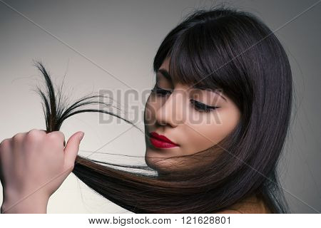 Beautiful young brunette holding hair and posing for a studio shot in the front of a grey background