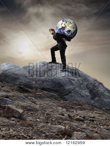 Businessman carrying the earth on his shoulders and climbing a rock