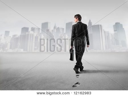 Businessman walking on the sand with cityscape on the background
