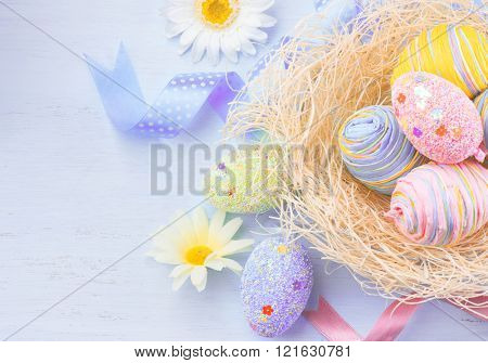 Easter colorful eggs background. Beautiful colorful eggs with decorations over violet wooden background, border design in pastel colors