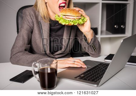 Woman eating burger while working