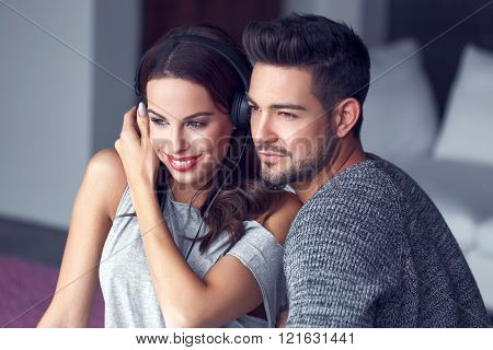 Happy Young Couple Listening To Music Indoor