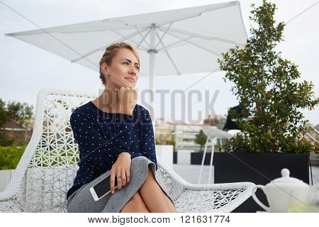 Thoughtful businesswoman is resting after conversation on mobile phone during free time
