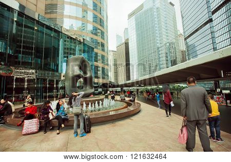 People Having Rest In Downtown With Scyscrapers And Modern Art Monuments
