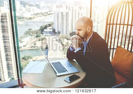 Concentrated and worried businessman sitting front open net-book in his office