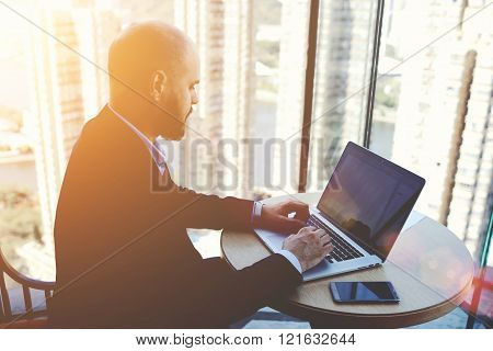 Successful male economist is analyzing the activities of the company via net-book