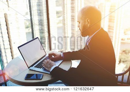 Male skilled accountant is checking the validity of the operation via net-book