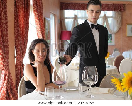 Waiter serving some wine to a beautiful woman in a luxury restaurant