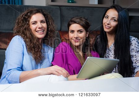 Three happy smiling female friends sharing a tablet computer