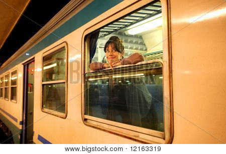 Smiling woman leaning against the window of a train in a railway station