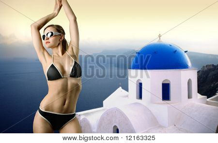 Beautiful woman in swimsuit with panorama of Santorini island on the background