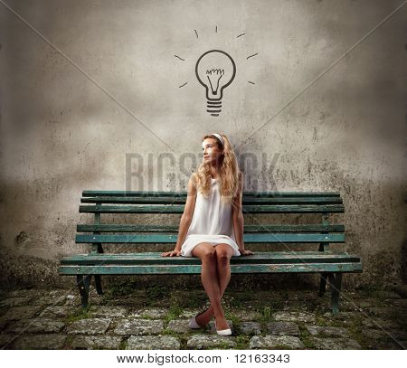 Young woman sitting on a park bench and having an idea