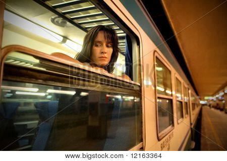 Sad woman leaning against the window of a train in a railway station