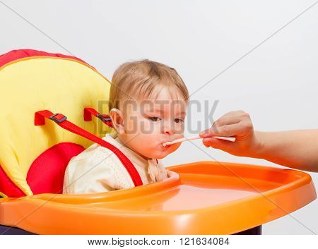 Baby Boy Eating With Spoon At Home