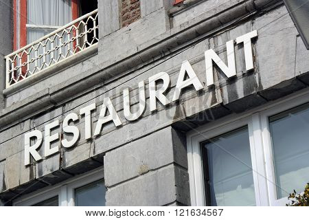 The word Restaurant at facade of old building in Wallonia, Belgium.