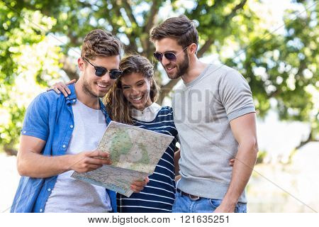 Hip friends checking map outdoors