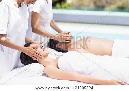 Couple receiving a face massage from masseur in a spa