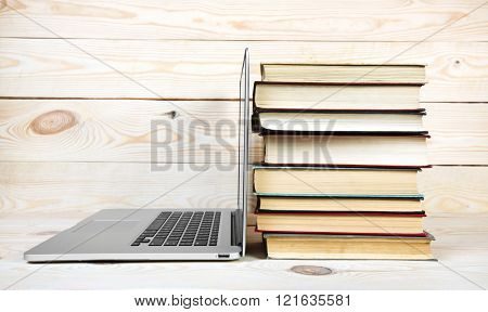 Stack of books and laptop on wooden table