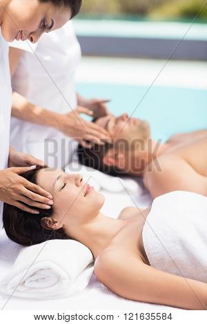 Couple receiving a head massage from masseur in a spa