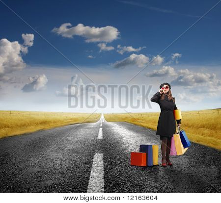 Elegant woman holding some shopping bags standing on a road