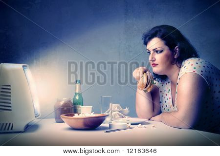 Fat woman dining in front of the television