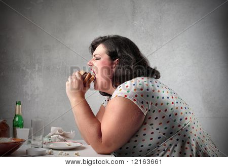 Fat woman eating a hamburger
