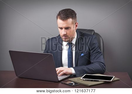 Handsome business man working with laptop in office